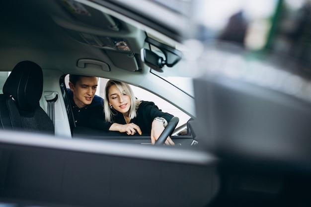 Potomstwo para wybiera samochód w samochodowym przedstawienie pokoju Darmowe Zdjęcia