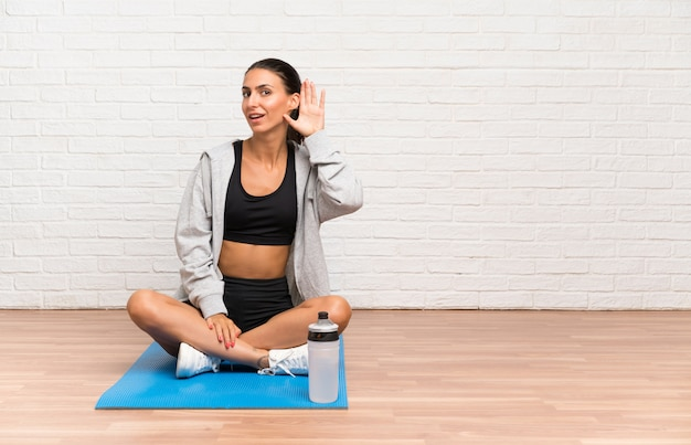 Potomstwo sporta kobiety obsiadanie na podłoga z matowym słuchaniem coś Premium Zdjęcia