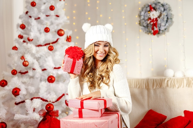Powabna kobieta pozuje z bożenarodzeniowymi prezentami Premium Zdjęcia
