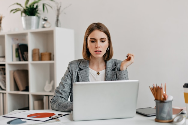 Poważna Biznesowa Kobieta Z Niepokojem Wygląda W Laptopie. Portret Dziewczynki Z Krótką Fryzurą W Białym Biurze. Darmowe Zdjęcia