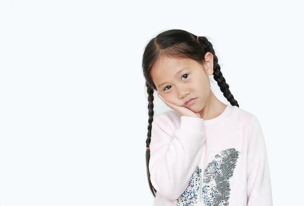 Poważna I Smutna Azjatycka Mała Dziewczynka Z Posturą Jej Rękę Na Policzku Premium Zdjęcia