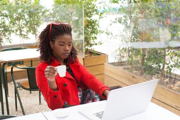 Poważna Kobieta Pije Kawę I Używa Laptop Darmowe Zdjęcia