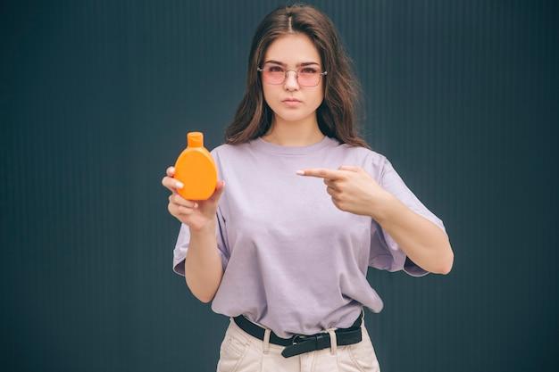 Poważna Kobieta Wskazująca Na Pomarańczową Butelkę Z Kremem Ochronnym Do Opalania W Butelce Z Spf Premium Zdjęcia