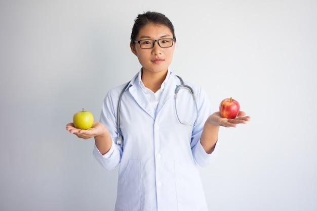 Poważna Młoda Azjatycka Kobiety Lekarki Mienia Czerwień I Kolor żółty Jabłko. Darmowe Zdjęcia