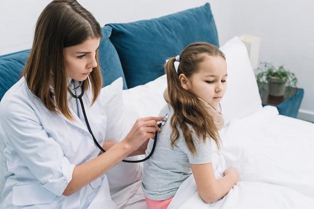 Poważna młoda kobiety lekarka egzamininuje dziewczyna plecy Darmowe Zdjęcia