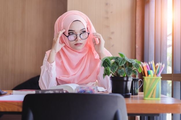 Poważnie azjatycka muzułmańska kobieta ma bóle głowy w biurze. Premium Zdjęcia