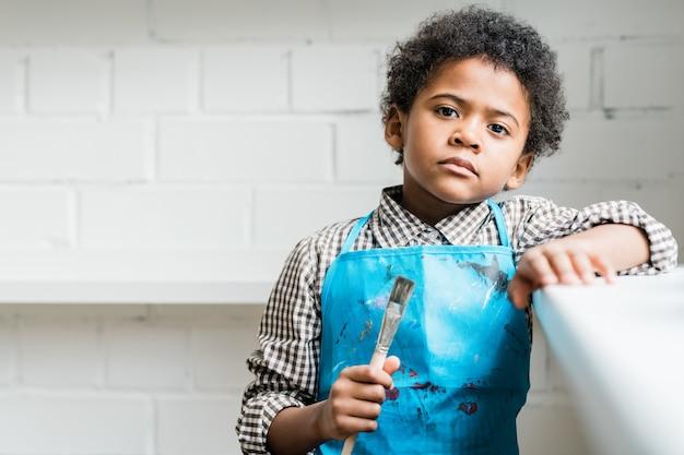 Poważny Afrykański Uczeń W Niebieskim Fartuchu, Trzymając W Ręku Pędzel, Stojąc Przed Kamerą W Studio Lub Klasie Premium Zdjęcia