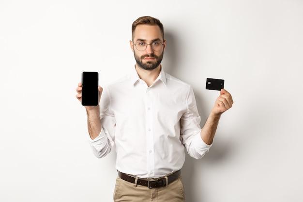 Poważny Biznesmen Pokazuje Ekran Telefonu Komórkowego I Kartę Kredytową. Koncepcja Zakupów Online. Darmowe Zdjęcia