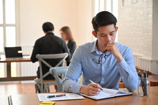 Poważny Biznesmen Pracuje Na Stole W Coworking Przestrzeni Premium Zdjęcia