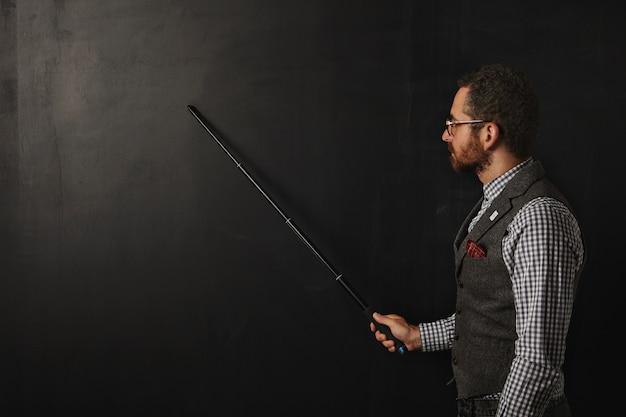Poważny Brodaty Profesor W Kraciastej Koszuli I Tweedowej Kamizelce, W Okularach, Pokazuje Coś Na Szkolnej Czarnej Tablicy Ze Złożoną Wskazówką Darmowe Zdjęcia