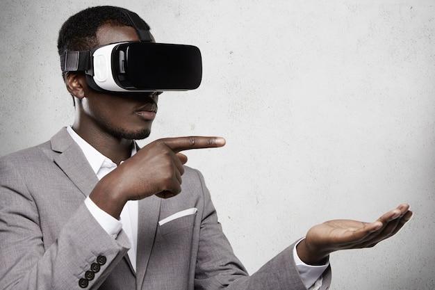Poważny Ciemnoskóry Przedsiębiorca W Formalnym Garniturze W Okularach Z Wyświetlaczem Na Głowie Dla Smartfona, Gestykulujący, Jakby Trzymał Coś Na Otwartej Dłoni I Wskazywał Palcem Na Przestrzeń Kopii Darmowe Zdjęcia
