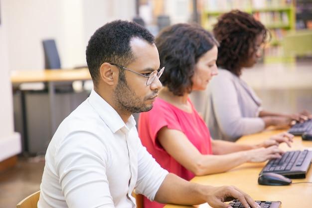Poważny Dorosły Męski Uczeń Studiuje W Komputer Klasie Darmowe Zdjęcia