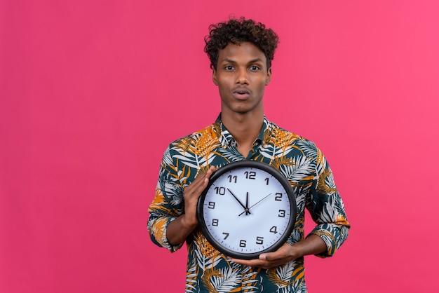 Poważny I Zdezorientowany Młody Przystojny Ciemnoskóry Mężczyzna Z Kręconymi Włosami W Koszulce Z Nadrukiem Liści Przedstawiającym Zegar ścienny Na Różowym Tle Darmowe Zdjęcia