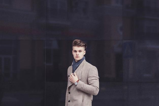 Poważny Mężczyzna W Stylowym Płaszczu Na ścianie Premium Zdjęcia