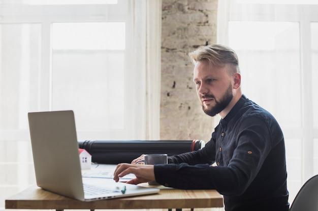 Poważny młody człowiek pracuje na laptopie przy biurem Darmowe Zdjęcia