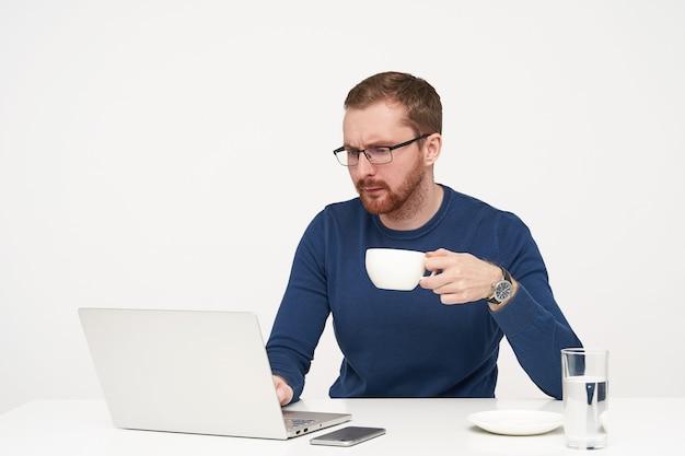 Poważny Młody Przystojny Brodaty Facet Trzyma Filiżankę Herbaty W Uniesionej Ręce, Patrząc Na Ekran Swojego Laptopa Z Skoncentrowaną Twarzą, Odizolowany Na Białym Tle Darmowe Zdjęcia