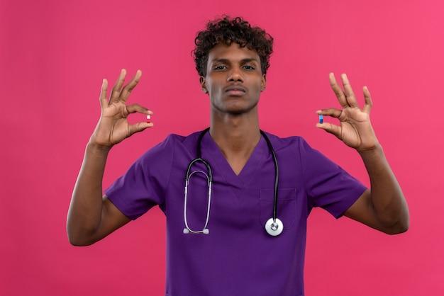 Poważny Młody Przystojny Ciemnoskóry Lekarz Z Kręconymi Włosami W Fioletowym Mundurze Z Pigułkami Trzymającymi Stetoskop Darmowe Zdjęcia