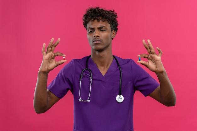 Poważny Młody Przystojny Ciemnoskóry Lekarz Z Kręconymi Włosami W Fioletowym Mundurze Ze Stetoskopem Patrząc Na Tabletki Darmowe Zdjęcia