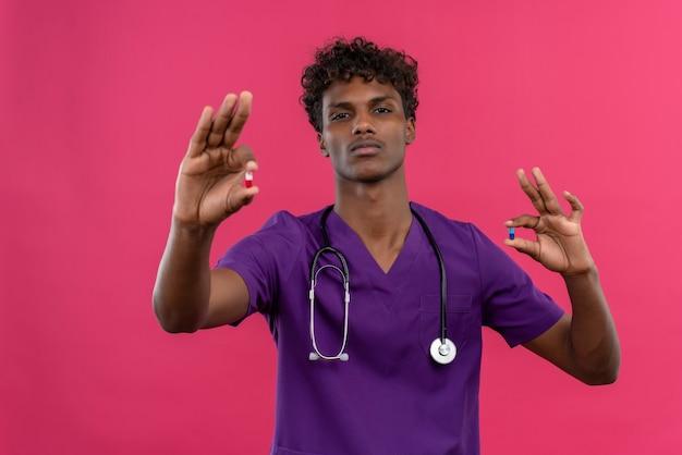 Poważny Młody Przystojny Ciemnoskóry Lekarz Z Kręconymi Włosami W Fioletowym Mundurze Ze Stetoskopem Pokazującym Tabletki Darmowe Zdjęcia