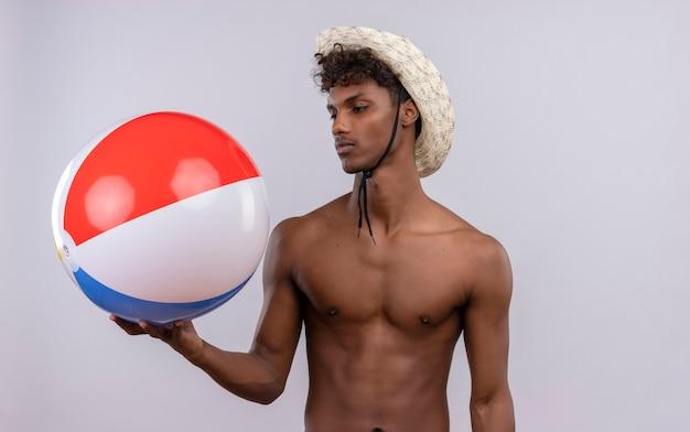 Poważny Młody Przystojny Ciemnoskóry Mężczyzna Z Kręconymi Włosami W Kapeluszu Przeciwsłonecznym, Patrząc Na Nadmuchiwaną Piłkę Darmowe Zdjęcia