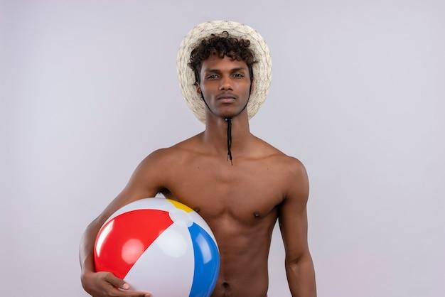 Poważny Młody Przystojny Ciemnoskóry Mężczyzna Z Kręconymi Włosami W Kapeluszu Przeciwsłonecznym, Trzymając Nadmuchiwaną Piłkę Darmowe Zdjęcia