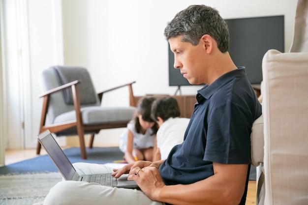 Poważny Profesjonalista Pracujący W Domu, Siedząc Na Podłodze I Używając Laptopa Darmowe Zdjęcia