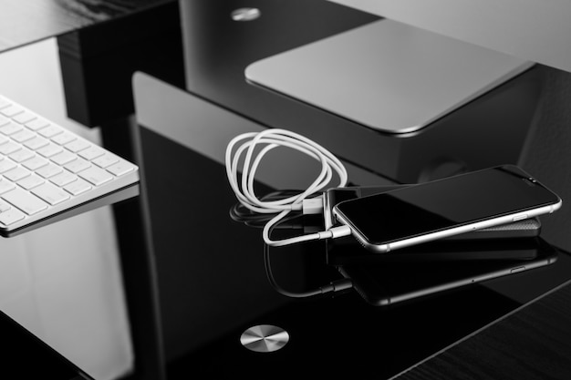 Power bank ładuje smartfon na eleganckim czarnym stole Premium Zdjęcia