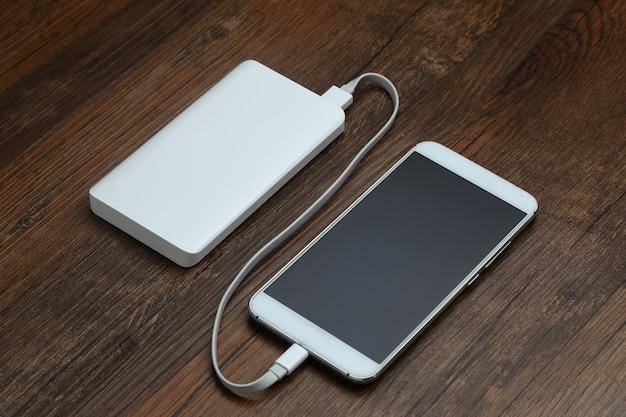Powerbank i telefon komórkowy na drewnianym stole Darmowe Zdjęcia