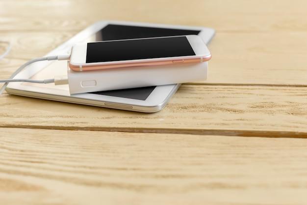 Powerbank i telefon komórkowy na drewnianym stole Premium Zdjęcia