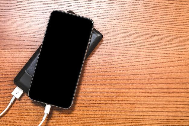 Powerbank ładuje smartphone odizolowywającego na drewnie Premium Zdjęcia