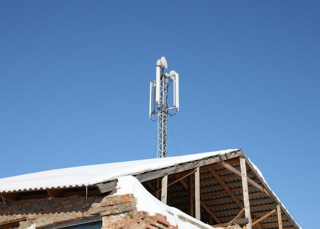 Powietrzna Komunikacja Mobilna Na Dachu Starego Domu Przeciw Niebieskiemu Niebu Premium Zdjęcia