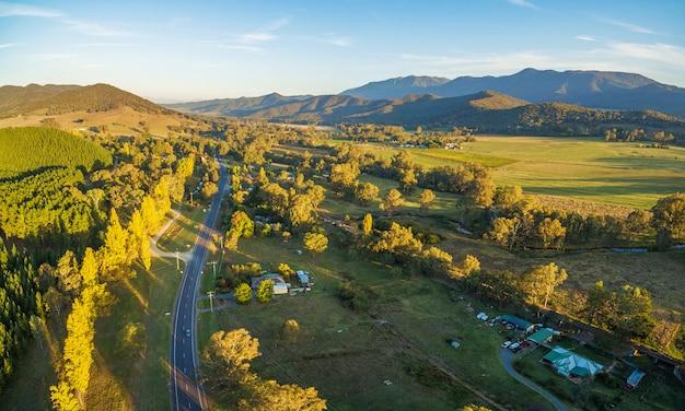 Powietrzny panoramiczny krajobraz wielkiej alpejskiej drogi przechodzi australijskiej wsi przy zmierzchem. victoria, australia Premium Zdjęcia