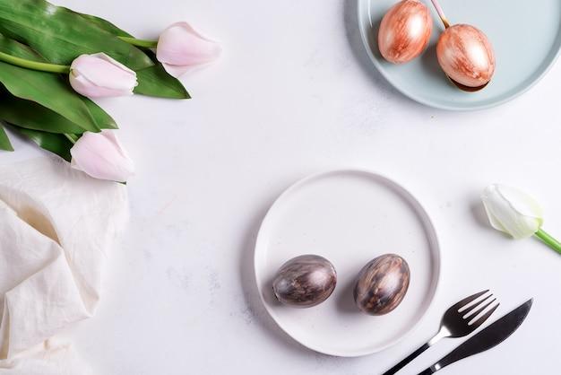 Powitanie Kartka Wielkanocna Z Ręcznie Malowanymi Jasnymi Jajkami Na Talerzach I Tulipanami Kwitnie Na Jasnoszarym Marmurowym Tle. Premium Zdjęcia
