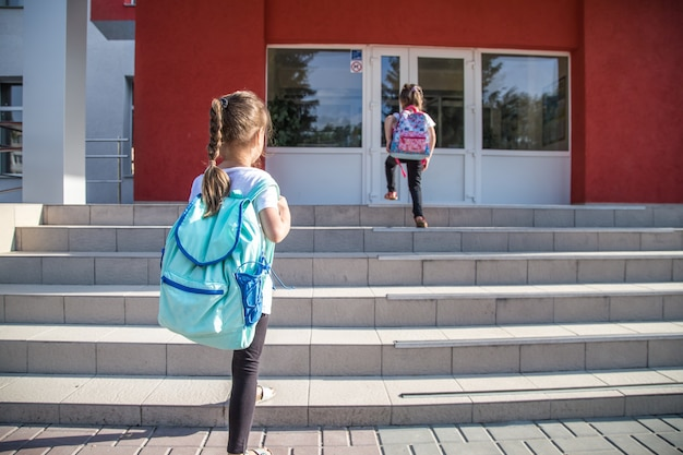 Powrót Do Koncepcji Edukacji Szkolnej Z Dziećmi Dziewczynki, Uczniów Szkół Podstawowych, Niosąc Plecaki Do Klasy Darmowe Zdjęcia