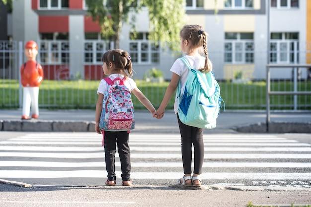 Powrót Do Koncepcji Edukacji Szkolnej Z Dziećmi Dziewczynki, Uczniów Szkół Podstawowych, Niosąc Plecaki Do Klasy Premium Zdjęcia