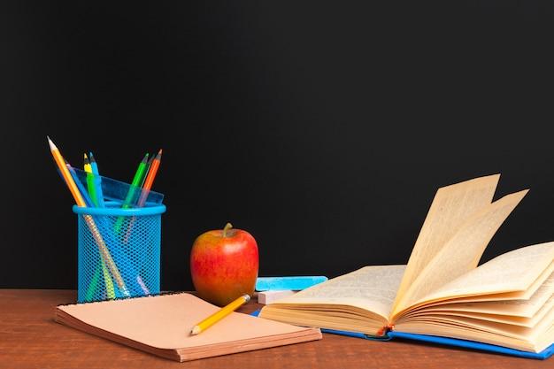 Powrót do koncepcji szkoły. tablica z książkami i jabłkiem na drewnianym biurku Premium Zdjęcia