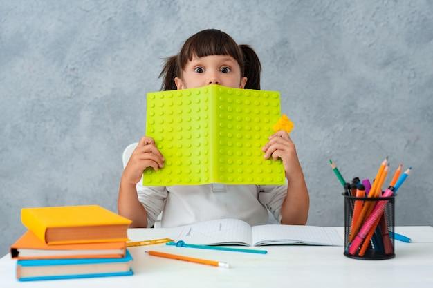 Powrót Do Szkoły. Słodkie Dziecko Uczennica Siedzi Przy Biurku W Pokoju. Darmowe Zdjęcia