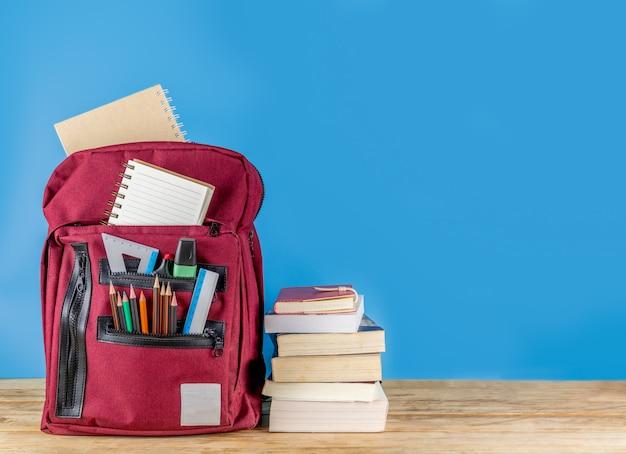 Powrót do szkoły . tornister i materiały na drewnianym stole z książkami Premium Zdjęcia