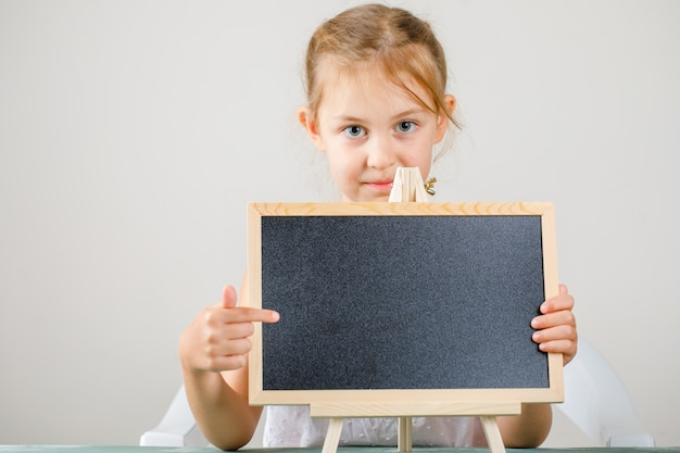 Powrót Do Widoku Z Boku Koncepcji Szkoły. Mała Dziewczynka Trzyma I Pokazuje Tablicę. Darmowe Zdjęcia