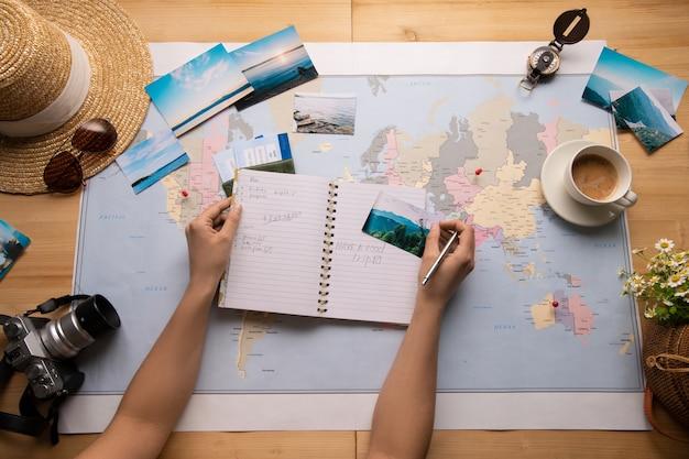 Powyżej Widok Kobiety Siedzącej Przy Stole Z Mapą świata I Robiącej Notatki O Zabytkach Premium Zdjęcia
