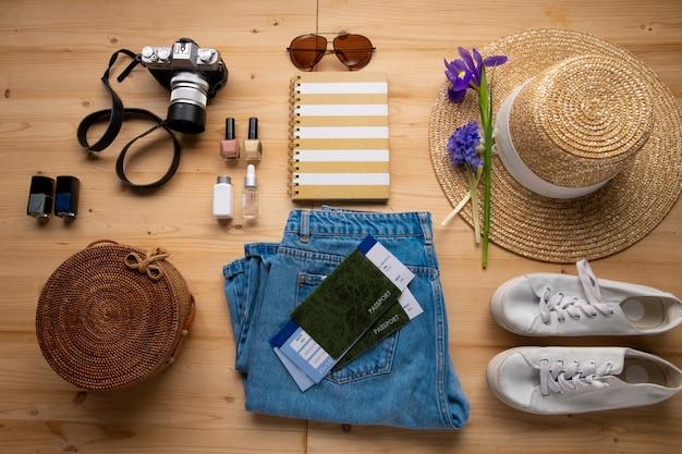 Powyżej Widok Na Dżinsy, Kapelusz Przeciwsłoneczny, Kwiat, Aparat Fotograficzny, Torbę, Bilety, Lakiery Do Paznokci I Trampki Na Stole, Podróże Na Knolling Premium Zdjęcia
