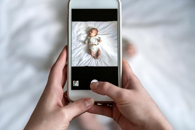 Powyżej Wysokiego Kąta Strzał Szczęśliwa Mama Robi Zdjęcie Jej Chłopca Lub Dziewczynkę W łóżku Ze Smartfonem W Domu Premium Zdjęcia