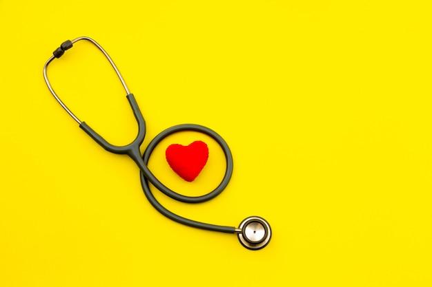 Powyżej Zdjęcia Stetoskopu Umieszcza Się Po Lewej Stronie Stołu Na żółtym Tle. Premium Zdjęcia