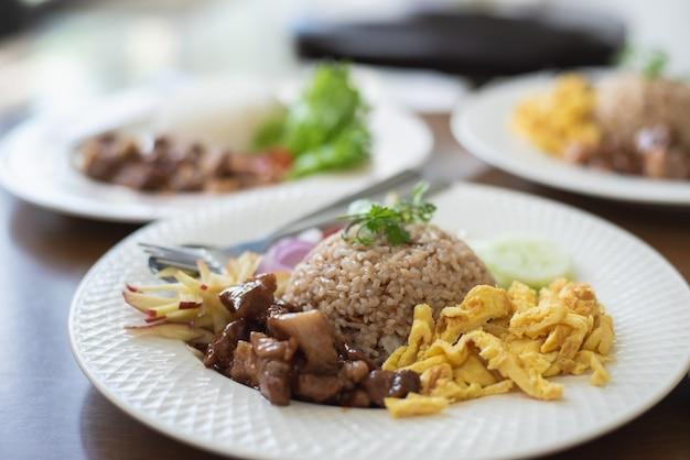 Pożarniczy ryż z wieprzowiną i podpalają jajko na drewno stole Premium Zdjęcia