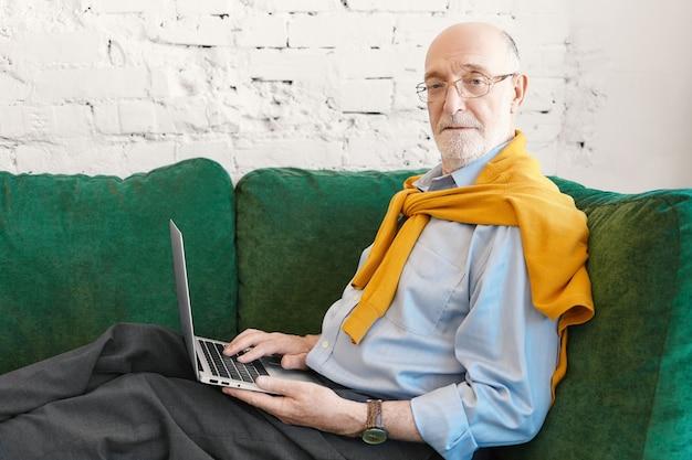 Poziome Poziome Portret Sześćdziesięcioletniego Brodatego Przedsiębiorcy W Okularach I Swetrze Nad Niebieską Koszulą, Pracującego Zdalnie, Siedzącego Na Kanapie Z Urządzeniem Elektronicznym Na Kolanach, Patrząc Na Kamery Darmowe Zdjęcia