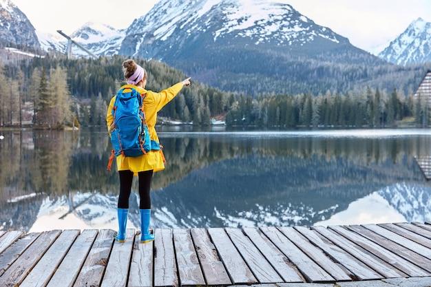 Poziome Strzał Kobiety Podróżnika W żółtym Płaszczu Przeciwdeszczowym I Niebieskich Kaloszach Stoi Przed Górskim Krajobrazem Darmowe Zdjęcia