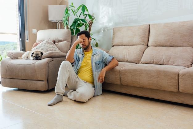 Poziome Strzał Mężczyzny Siedzącego Na Podłodze W Domu Z Wyrazem Zmęczenia Darmowe Zdjęcia