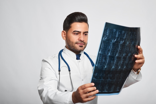 Poziome Strzał Przystojny Brodaty Mężczyzna Hispanic Lekarza Badającego Lookig Skanowania Rentgenowskiego Poważne I Skoncentrowane Sprawdzanie Koncentracji Badanie Medyczne Badanie Kliniczne Koncepcja Profesjonalizmu Leczenia. Premium Zdjęcia