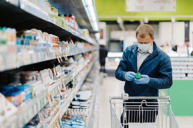 Poziome Ujęcie Dorosłego Mężczyzny Nosi Maskę Ochronną, Czyta Etykietę Produktu, Robi Zakupy Podczas Wybuchu Koronawirusa, Kupuje Niepotrzebne Jedzenie W Lokalnym Sklepie. Ludzie, Wirus, Choroba, Koncepcja Zakupów Premium Zdjęcia