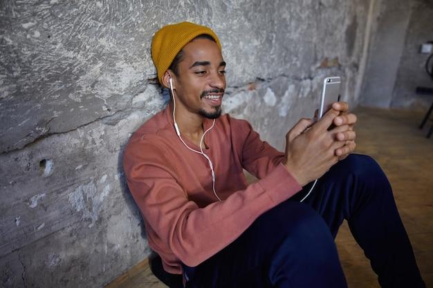 Poziome Ujęcie Pozytywnego Brodatego Ciemnoskórego Faceta W Różowym Swetrze, Niebieskich Spodniach, Spodniach I Musztardowej Czapce, Siedzącego Na Drewnianej Podłodze Ze Smartfonem W Rękach I Słuchającego Muzyki Przez Słuchawki Darmowe Zdjęcia
